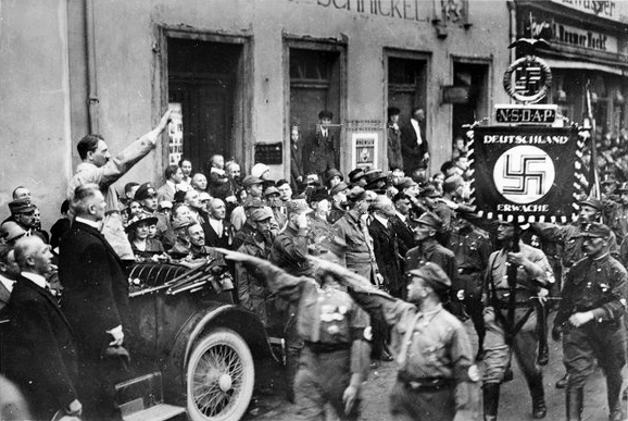 Adolf Hitler in his car in front of the parade of the SA during the second party rally in Weimar