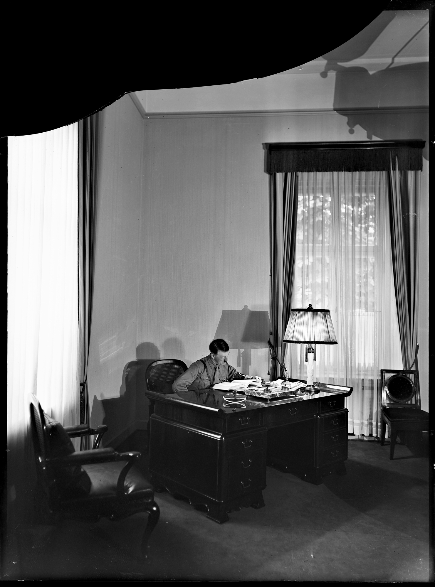 Adolf Hitler in his office of Munich's Braunes Haus a few days after the opening of the building (Heinrich Hoffmann photo)