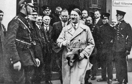 Adolf Hitler leaves the regional court in Frankenthal. The photo was manipulated and an Adolf Hitler Straße plaque was added to create a postcard in 1933