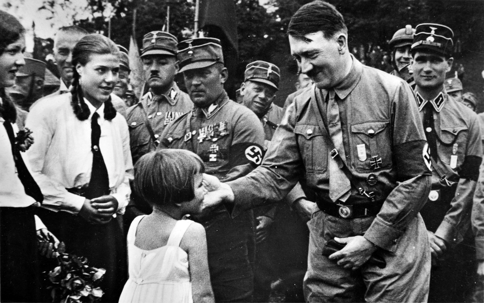 A little girl is offering Adolf Hitler a small bouquet during Gera's Gauparteitag