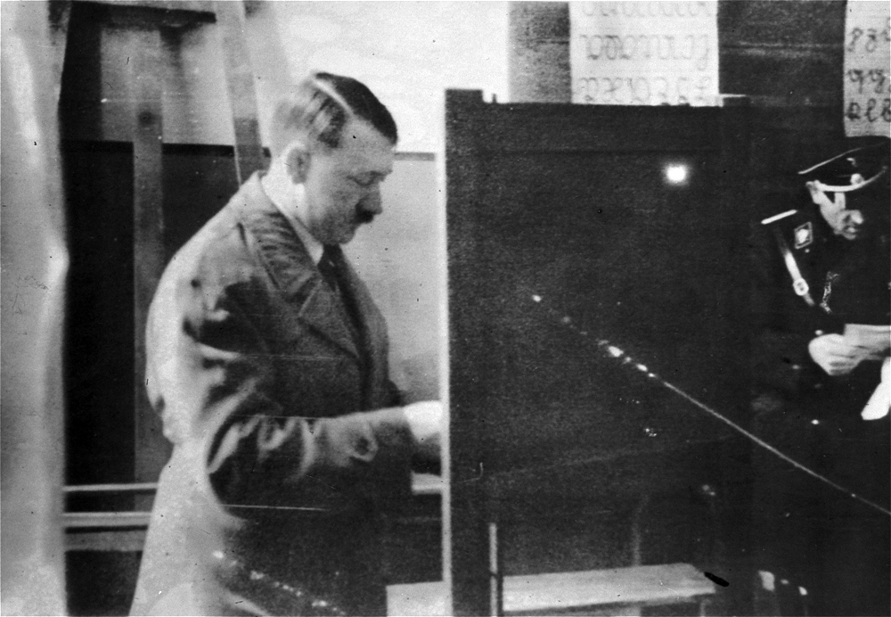 Adolf Hitler casts his vote at a polling station set up in a schoolroom for the Reichstag elections