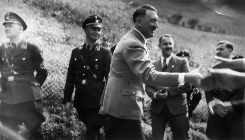 Adolf Hitler greets people outside of Haus Wachenfeld during one of the many times visitors could come and see him on the Obersalzberg