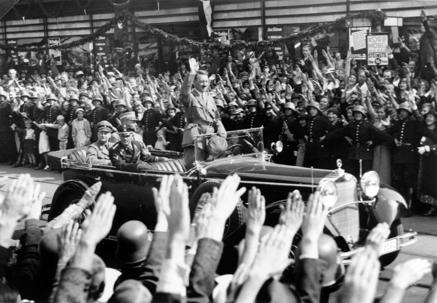 Standing in an open car, Adolf Hitler salutes a crowd lining the streets of Hamburg
