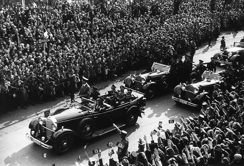 Adolf Hitler is standing in his open car while driving through Köln (Cologne)