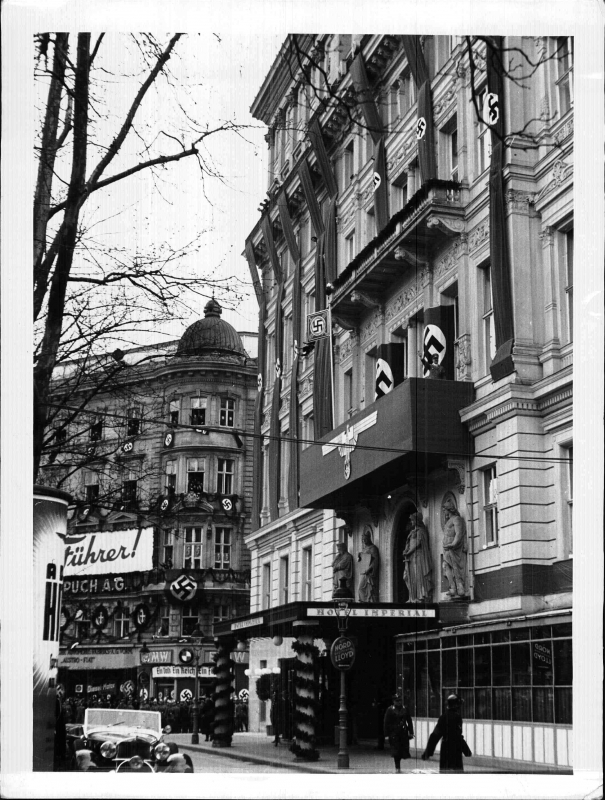 Adolf Hitler salutes from the balcony of the Hotel Imperial in Vienna