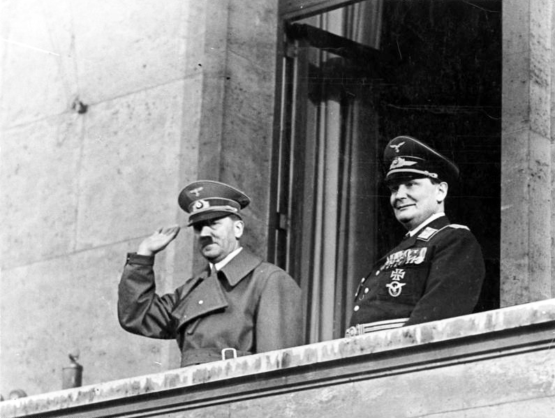 Adolf Hitler and Hermann Göring salute the crowd from the chancellery balcony at his return after the Anschluss