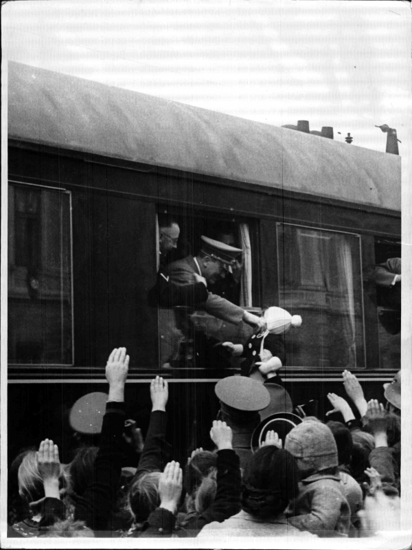 Adolf Hitler in his train greets people at Salzburg station
