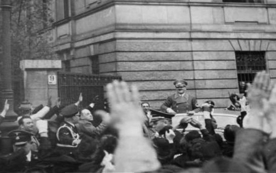 Adolf Hitler greets the crowd in front of the Italian embassy in Vienna
