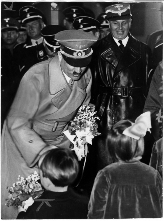 Adolf Hitler is greeted by children as he leaves Berlin's Anhalter station at his return from Austria