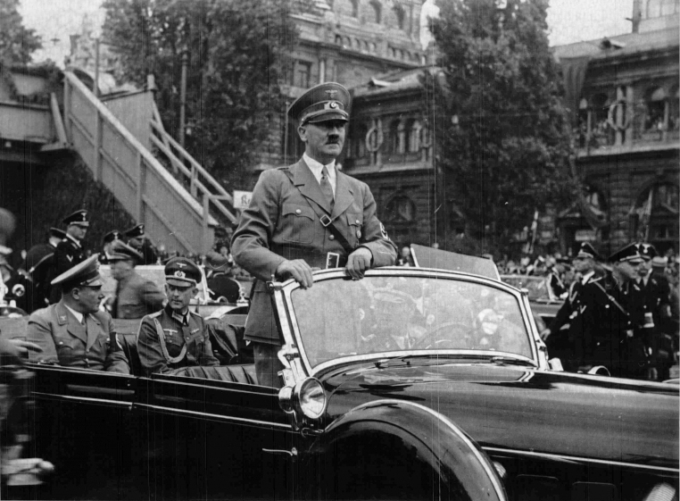 Hitler standing in his car as he travels through the ancient town of Nuremberg to open the Party Congress
