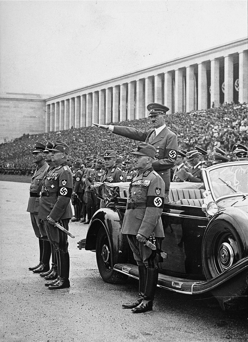 Formations of the Reich Labour Service parading past Adolf Hitler at the rally ground