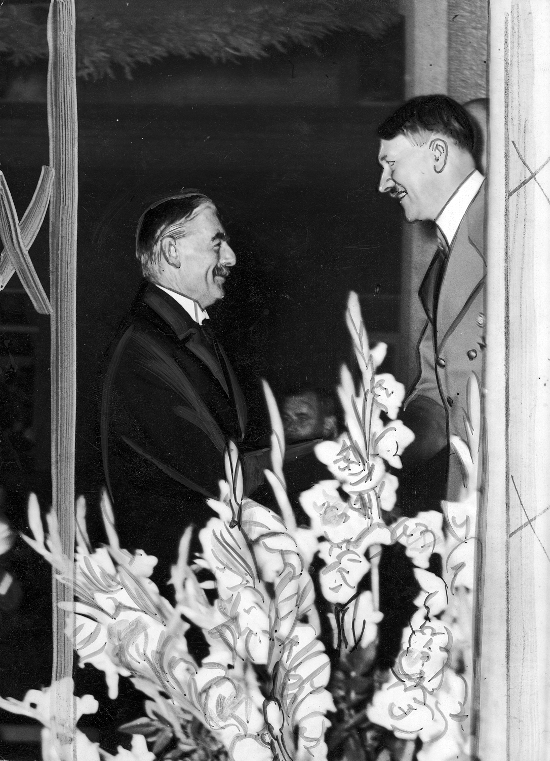 British prime minister Neville Chamberlain and Adolf Hitler shake hands during Chamberlain's visit to Germany