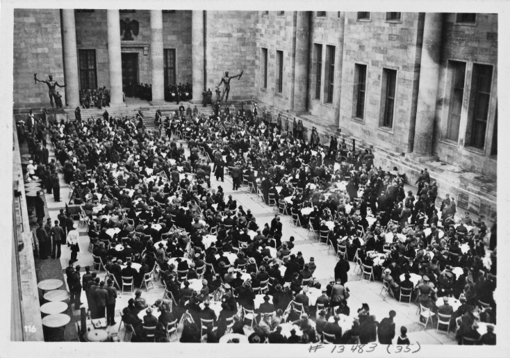 In the courtyard of the new Reich Chancellery, Adolf Hitler shares the Eintopf with invited citizens
