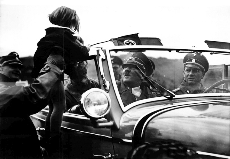 Adolf Hitler greets a child from his car during his tour to the Westwall installations