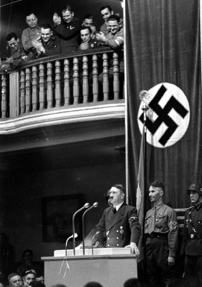 Adolf Hitler speaking to participants of the 1923 Beer Hall Putsch just before the failed bombing attempt by Georg Elser. The bomb was placed in the pillar behind Hitler.