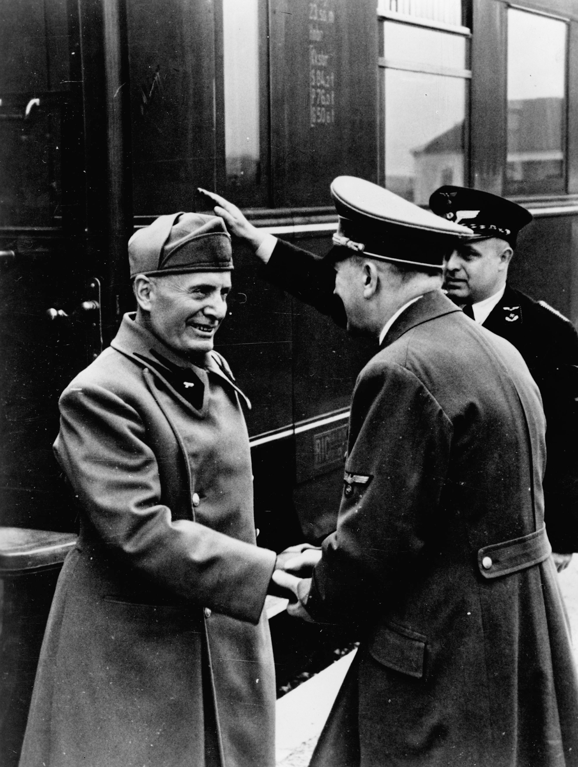 Adolf Hitler greets Benito Mussolini as he arrives at the train station before their meeting at Schloss Kleßheim