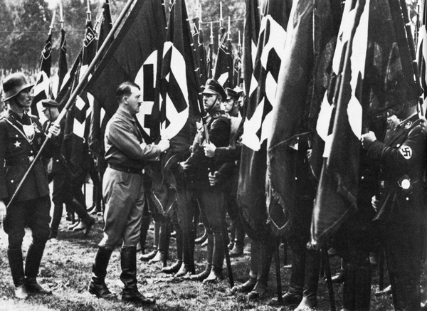 Adolf Hitler consecrating the standards at the 1933 Nuremberg Party Rally with Jakob Grimminger holding the Blood flag behind him