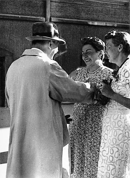 Adolf Hitler speaks with two women in front of his apartment on Prinzregentenplatz in Munich