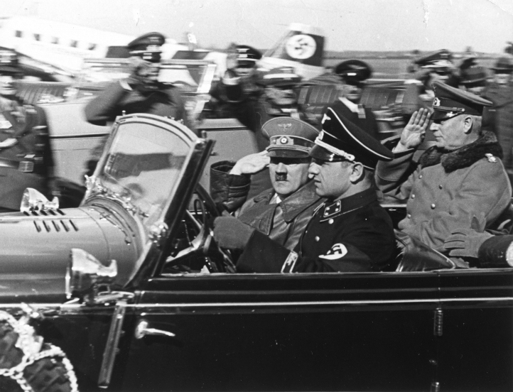 Adolf Hitler and Wilhelm Keitel arrive in an open car at Munich's airport before their flight to Austria