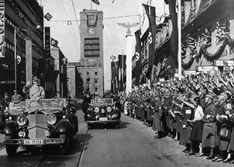 Adolf Hitler crosses Stuttgart and greets the crowd on his way to make a speech in the city hall