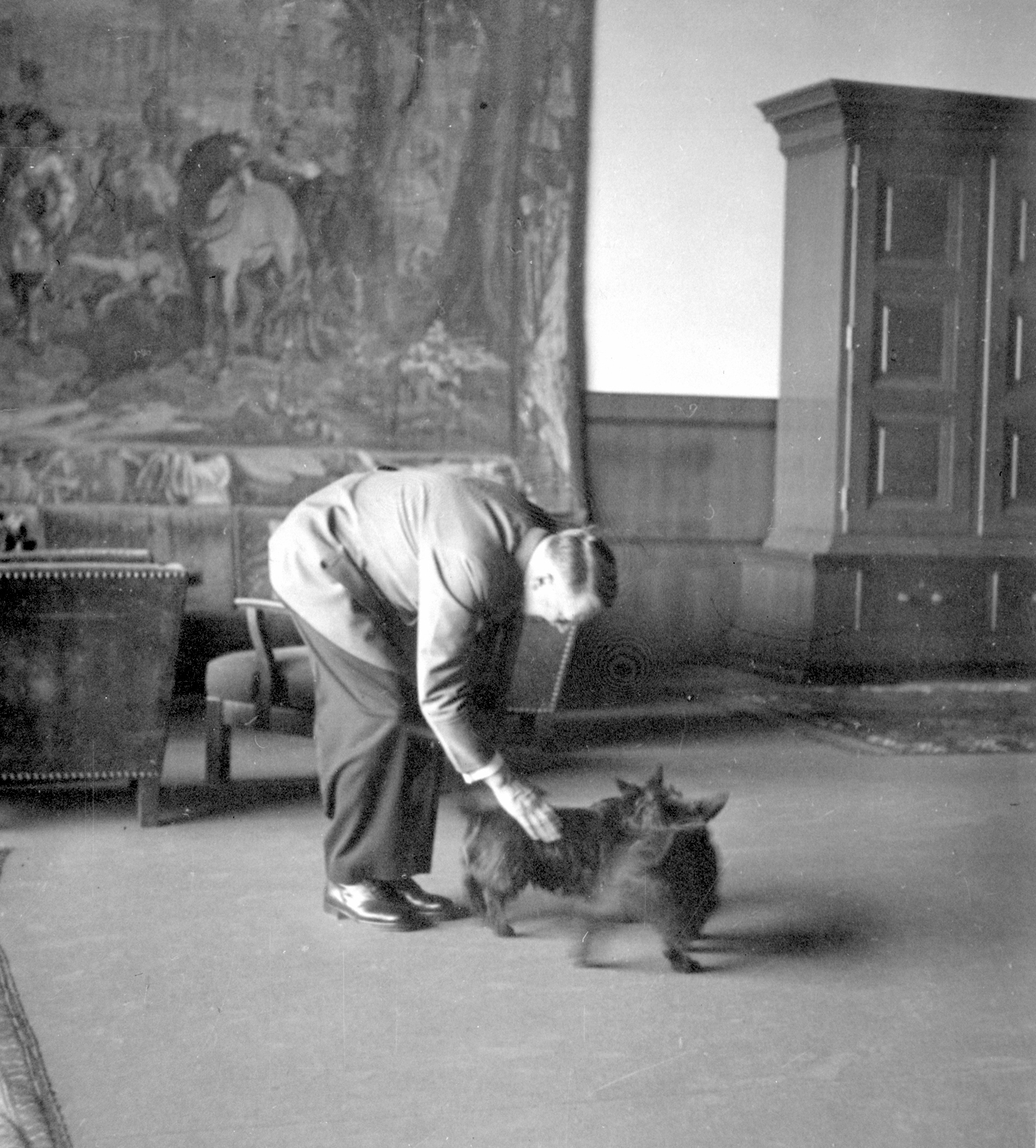 Adolf Hitler petting Eva Braun's dogs in the Berghof great hall, from Eva Braun's albums