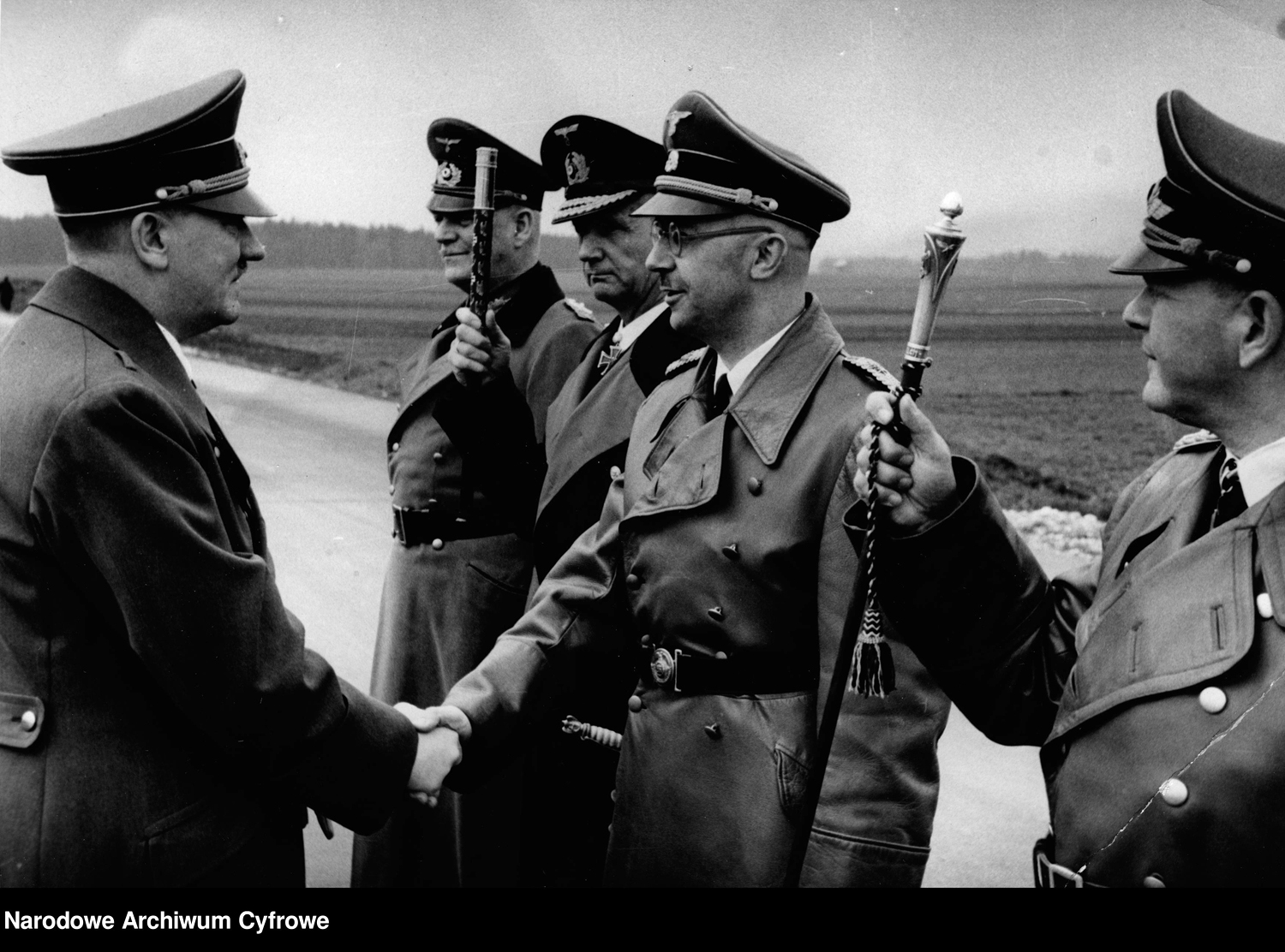 Adolf Hitler greets Heinrich Himmler on the day on his 55th birthday, near Schloss Klessheim